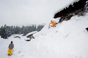雪の五箇山合掌集落で屋根の雪下ろしの写真素材 [FYI01635042]