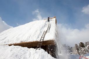 雪の白川郷合掌集落で屋根の雪下ろしの写真素材 [FYI01635140]