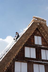 雪の白川郷合掌集落で屋根の雪下ろしの写真素材 [FYI01635142]