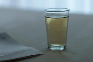 お茶のグラスと英字新聞の写真素材 [FYI01635364]