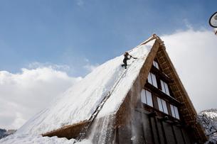 雪の白川郷合掌集落で屋根の雪下ろしの写真素材 [FYI01635513]