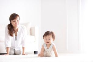 リビングでハイハイをする赤ちゃんと母親の写真素材 [FYI01635644]