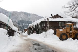 雪の白川郷合掌集落と除雪車の写真素材 [FYI01635701]
