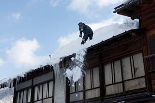 雪の白川郷合掌集落で屋根の雪下ろしの写真素材 [FYI01636007]