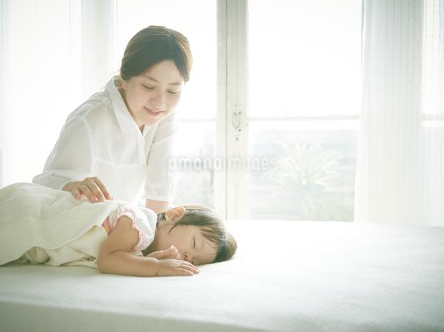 ベッドの上でお昼寝する赤ちゃんをお母さんが優しく見つめているの写真素材 [FYI01637199]