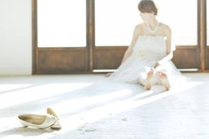 窓際に座り込む新婦と靴の写真素材 [FYI01637202]