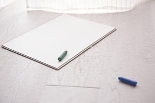 窓際に置いてあるスケッチブックとクレヨンの写真素材 [FYI01637235]