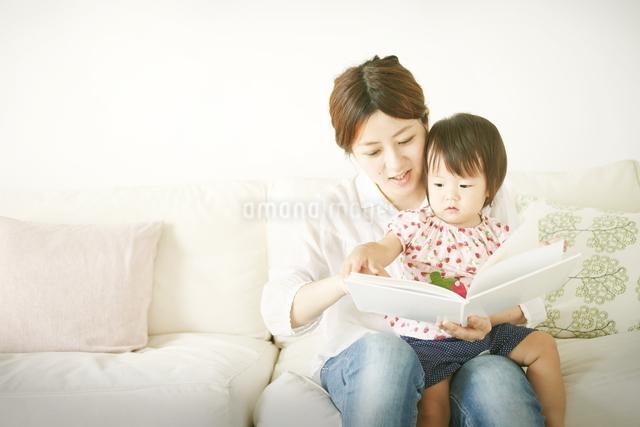 お母さんが赤ちゃんに本を読み聞かせているの写真素材 [FYI01637263]