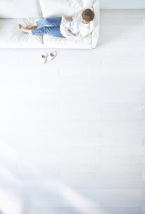白い床のリビングにあるソファーに座る女性の写真素材 [FYI01637364]