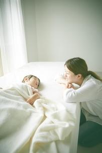 ベッドの上でお昼寝する赤ちゃんをお母さんが優しく見つめているの写真素材 [FYI01637371]