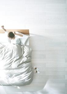白い床の寝室にあるベットで起床した女性の写真素材 [FYI01637372]