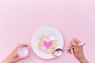 愛のサプリメントを食べようとする女性の写真素材 [FYI01637470]