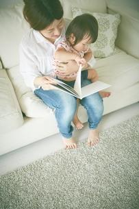 おかあさんが赤ちゃんに本を読み聞かせているの写真素材 [FYI01637557]