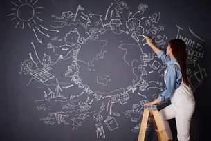 黒板に地球の絵を描く女性のイラスト素材 [FYI01637569]