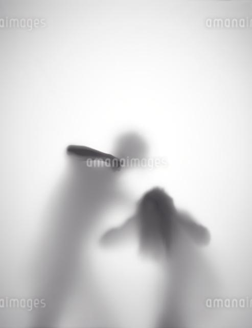 男が女性を殴ろうとしているシルエットの写真素材 [FYI01637574]