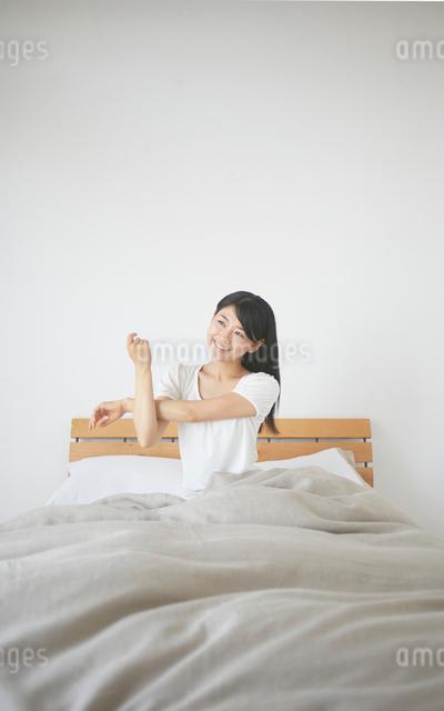 ベッドの上でストレッチをする女性の写真素材 [FYI01637590]