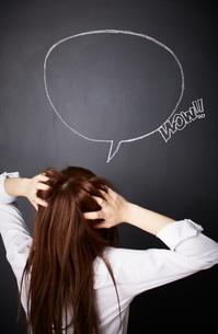 黒板に描かれた吹き出しの前で頭を抱える女性のイラスト素材 [FYI01637604]