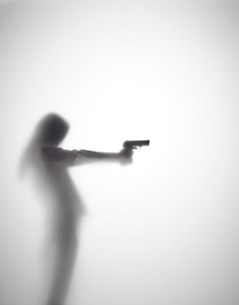 銃を持つ女性のシルエットの写真素材 [FYI01637606]