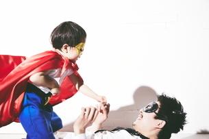 悪者をやっつけているヒーローの男の子の写真素材 [FYI01637704]