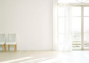 窓辺の白い壁と床に置いてある椅子二脚の写真素材 [FYI01637733]