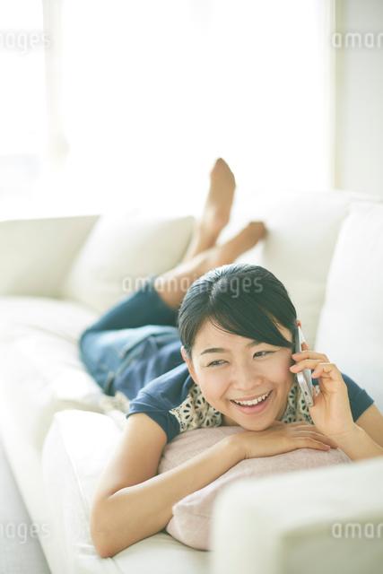 ソファーの上で電話している女性の写真素材 [FYI01637749]