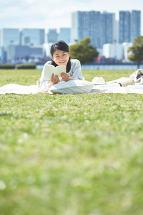 公園で読書をする女性の写真素材 [FYI01637792]