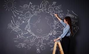 黒板に地球の絵を描く女性のイラスト素材 [FYI01637798]