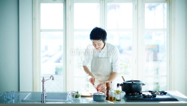 キッチンで料理をする男性の写真素材 [FYI01637841]