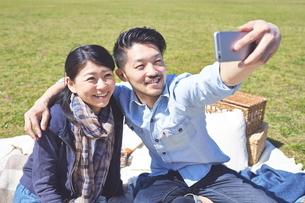 公園でピクニックをするカップルの写真素材 [FYI01637897]