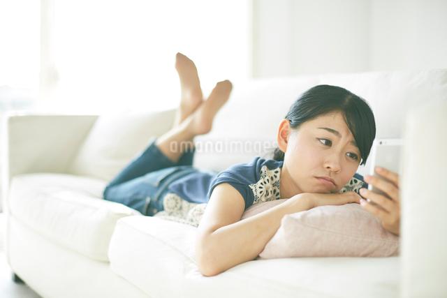 ソファーの上で携帯を見ながら寂しそうな顔をしている女性の写真素材 [FYI01637987]