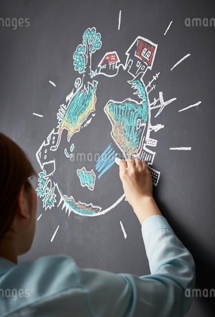 黒板に地球の絵を描く女性のイラスト素材 [FYI01637990]