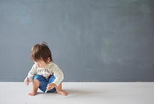 黒板の前でチョークを見つめている赤ちゃんの写真素材 [FYI01638007]