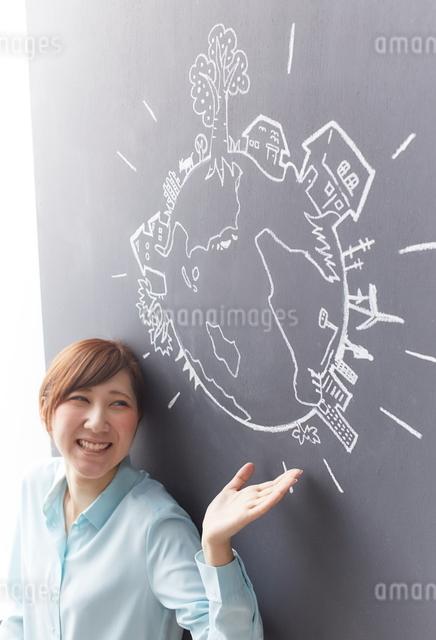 黒板に描かれた地球の絵を見せる女性のイラスト素材 [FYI01638035]