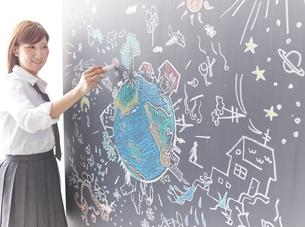 黒板に地球を描く女性のイラスト素材 [FYI01638036]