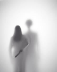 男に襲われそうになっている女性が背後に包丁を持つシルエットの写真素材 [FYI01638042]