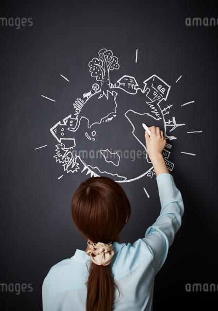 黒板に地球を描く女性のイラスト素材 [FYI01638064]
