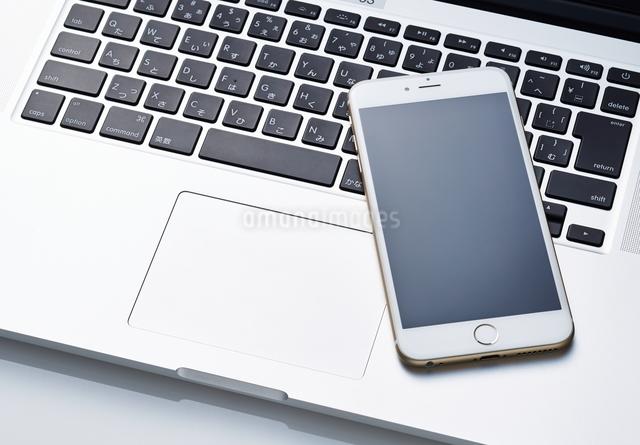 パソコンの上にあるスマートフォンの写真素材 [FYI01638066]