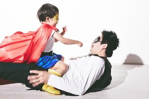 悪者をやっつけているヒーローの男の子の写真素材 [FYI01638102]