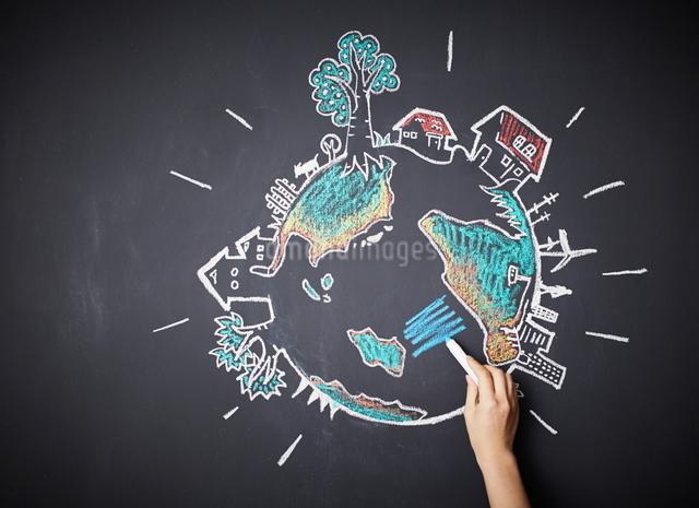 黒板に地球の絵を描く女性のイラスト素材 [FYI01638145]
