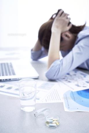 パソコンの前で頭を抱える女性とサプリメントの写真素材 [FYI01638241]
