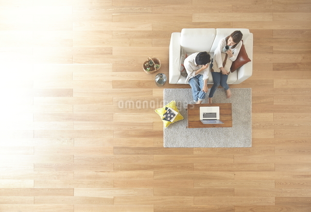 茶色の木の床とコーヒを飲む夫婦の写真素材 [FYI01638265]