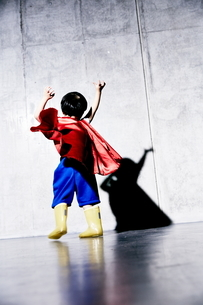 コンクリートの壁の前でポーズをキメるヒーローの男の子の写真素材 [FYI01638271]