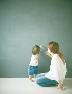 黒板にお絵かきをしている親子の写真素材 [FYI01638295]