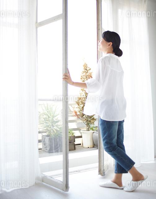 窓を開ける女性の写真素材 [FYI01638338]