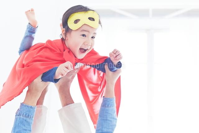 パパに飛行機をしてもらっているちびっこスーパーマンの写真素材 [FYI01638353]