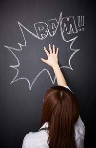 黒板に描かれた吹き出しの上をたたく女性のイラスト素材 [FYI01638359]