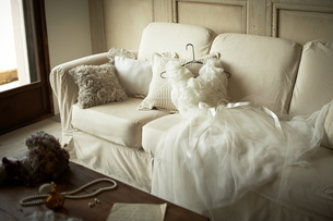 ソファーの上に置かれたウエディングドレスの写真素材 [FYI01638378]