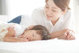 お昼寝しているあかちゃんを優しくみつめるお母さんの写真素材 [FYI01638391]