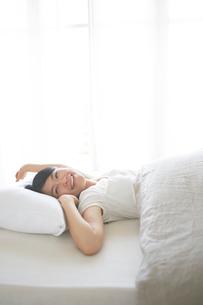 ベッドの上でストレッチをする女性の写真素材 [FYI01638445]