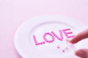 お皿に乗った愛のサプリメントを手に取る女性の写真素材 [FYI01638454]
